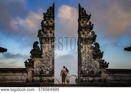 Happy Young Couple Staying In Temple Gates Of Heaven And Holding Hands Of Each Other. Perfect Honeym