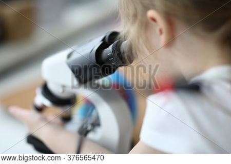Close-up Of Cute Child Investigating Sample Under Modern Microscope. Kid Having Fun With Research In