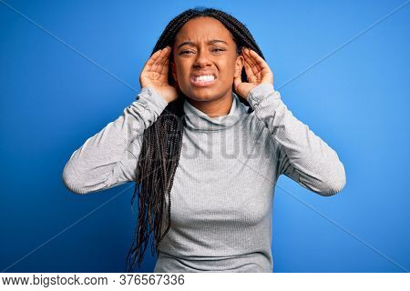 Young african american woman standing wearing casual turtleneck over blue isolated background Trying to hear both hands on ear gesture, curious for gossip. Hearing problem, deaf