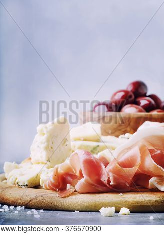 Snacks Or Antipasti, Crostini, Prosciutto, Blue Cheese And Olives, Gray Background, Selective Focus