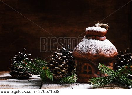 Christmas House From Clay With Pine Cones And Fir Branches Under The Snow, Vintage Wooden Background