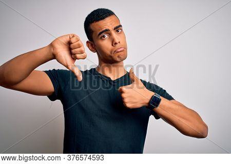 Young handsome african american man wearing casual t-shirt standing over white background Doing thumbs up and down, disagreement and agreement expression. Crazy conflict