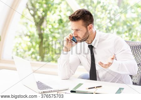 Shot Of Confused Businessman Wearing Shirt And Tie While Sitting At Office Desk And Working. Profess