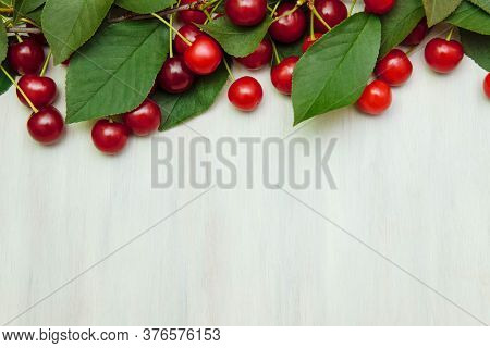 Frame Of Branches With Green Leaves And Red Ripe Cherries On A White Wooden Background With An Empty