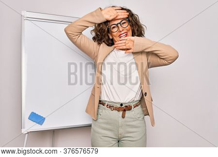 Middle age senior business woman standing on seminar presentation by magnectic blackboard Smiling cheerful playing peek a boo with hands showing face. Surprised and exited