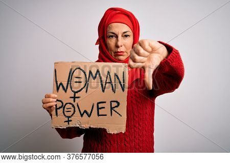 Middle age woman wearing muslim hijab asking for women rights holding banner with angry face, negative sign showing dislike with thumbs down, rejection concept