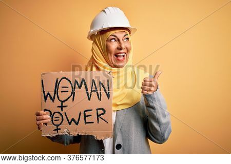 Middle age architect woman wearing muslim hijab holding banner with women message pointing and showing with thumb up to the side with happy face smiling