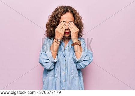 Middle age beautiful woman wearing casual denim shirt standing over pink background rubbing eyes for fatigue and headache, sleepy and tired expression. Vision problem