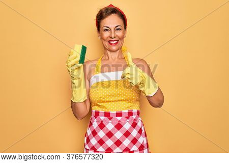 Middle age senior housewife pin up woman wearing 50s style retro dress using cleaner scrub happy with big smile doing ok sign, thumb up with fingers, excellent sign