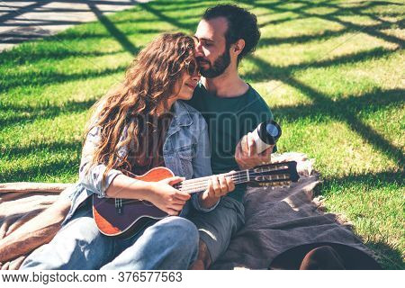 Beautiful Smiling Couple Enjoying Each Other On Picnic Day In The Modern Park. Teaches To Play Ukule