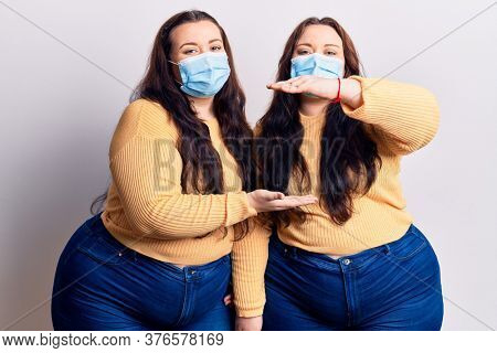 Young plus size twins wearing medical mask gesturing with hands showing big and large size sign, measure symbol. smiling looking at the camera. measuring concept.