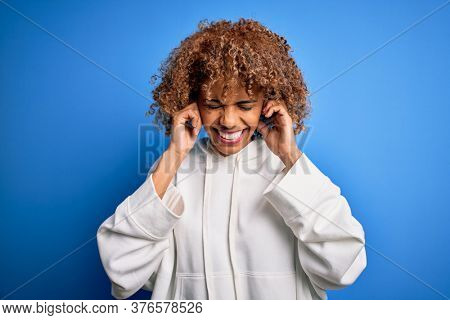 Beautiful african american sporty woman wearing casual sweatshirt over blue background covering ears with fingers with annoyed expression for the noise of loud music. Deaf concept.