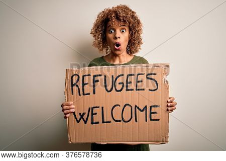 African american woman asking for immigration holding banner with wlecome refugees message scared in shock with a surprise face, afraid and excited with fear expression