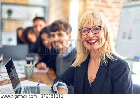 Group of business workers sitting in line with smile on face. Looking at the camera, middle age woman smiling at the office