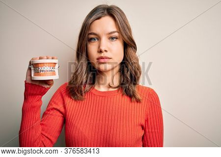 Young blonde girl holding orthodontist prosthesis denture over isolated background with a confident expression on smart face thinking serious