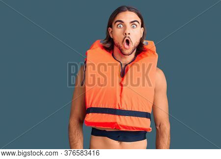 Young handsome man wearing nautical lifejacket afraid and shocked with surprise expression, fear and excited face.