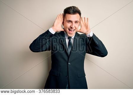 Young handsome business man wearing elegant suit and tie over isolated background Smiling cheerful playing peek a boo with hands showing face. Surprised and exited