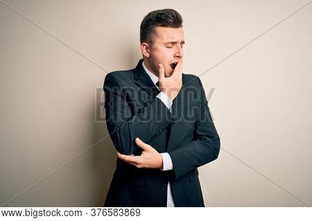 Young handsome business man wearing elegant suit and tie over isolated background bored yawning tired covering mouth with hand. Restless and sleepiness.