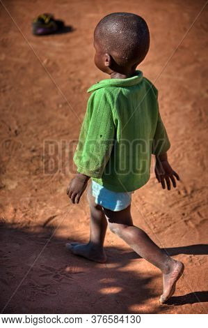 small African child strolling through the hot sand, Botswana village