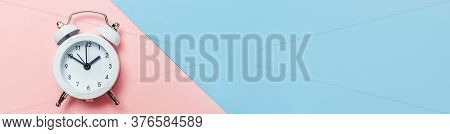 Simply Minimal Design Ringing Twin Bell Classic Alarm Clock Isolated On Blue Pink Pastel Background.