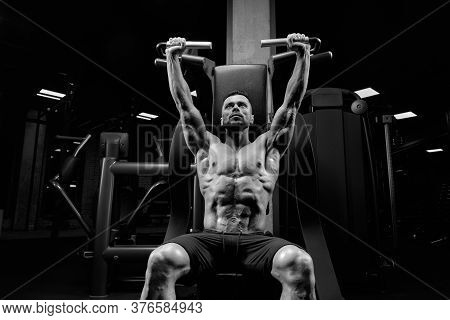 From Below View Of Handsome Muscular Man Sitting On Simulator In Empty Gym. Monochrome Portrait Of S