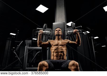 From Below View Of Bearded Muscular Man Sitting On Simulator In Empty Gym. Portrait Of Shirtless Bod