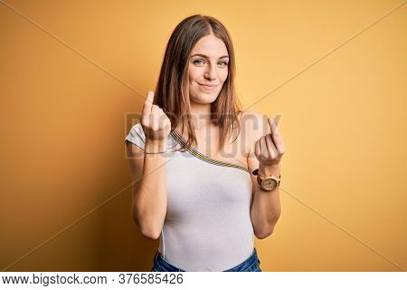 Young beautiful redhead woman wearing casual t-shirt over isolated yellow background doing money gesture with hands, asking for salary payment, millionaire business