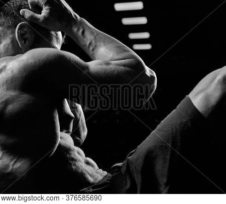 Black And White Crop Of Muscular Caucasian Man Training Abs On Mat In Gym. Side View Of Incognito Sp