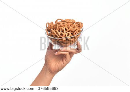 Hand of caucasian young man holding bowl with baked pretzels over isolated white background