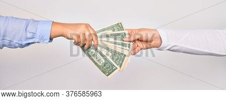 Two hands of caucasian young women doing transaction. Woman giving bunch of dollars banknote to other person over isolated white background