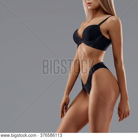 Side Crop Of Incognito Sexy Caucasian Female Model Wearing Black Lingerie Standing, Isolated On Grey