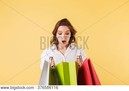 Portrait Of Young Astonished Lady Standing With Colorful Shopping Bags In Hands And Amazedly Looking