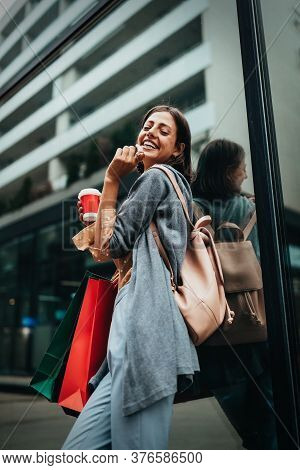 Happy Young Woman Drinking Take Away Coffee And Walking With Bags After Shopping In City.