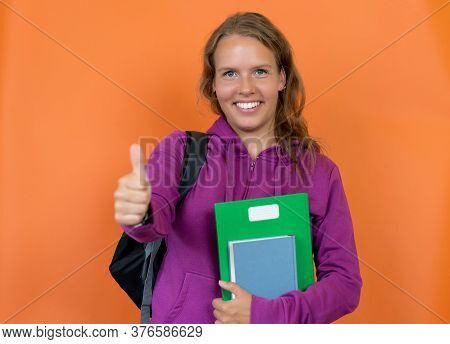 Pretty Blond German Female Student With Hoody Showing Thumb Up Isolated On Orange Background