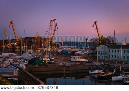 Beautiful Colorful Sunset Port Area With Portal Cranes, Yachts And Boats In Klaipeda, Lithuania.