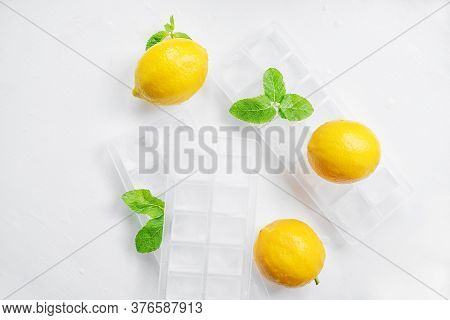 Lemons, Mint And Ice On A White Table. Ingredients For Cooling Homemade Lemonade. Top View.