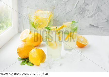 Two Foggy Glasses And A Decanter With Homemade Lemonade And Lemons On A White Table By The Window. C