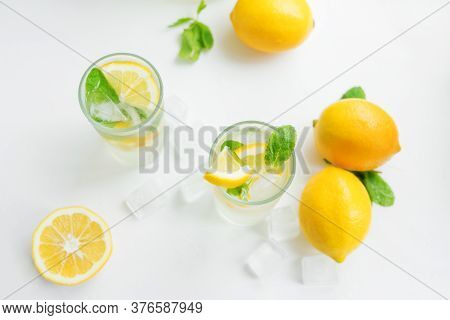 Two Foggy Glasses And A Decanter With Homemade Lemonade And Lemons On A White Table. Cooling Drink I