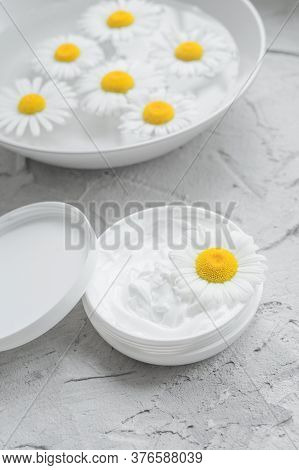 Chamomile Natural Cream. Chamomile In An Opened Jar With White Face And Body Cream. Plate With Chamo