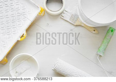Tools For Painting Walls: Roller, Tray, Paint Bucket, Brush, Masking Tape, Putty On A White Wooden B