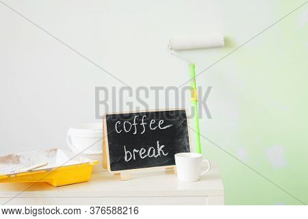 Tools For Painting Walls: Roller, Tray, Paint, Brush And Cup Of Coffee On A White Wall Background. I