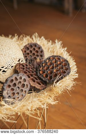 Dried Lotus Seed Pods On Brim Straw Hat In The Interior.