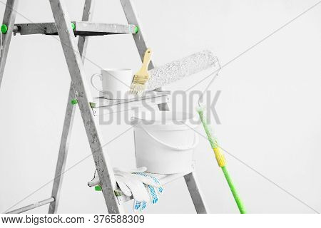 Tools For Painting Walls: Roller, Tray, Bucket Of Paint, Brush, Gloves And A Cup Of Coffee On A Step