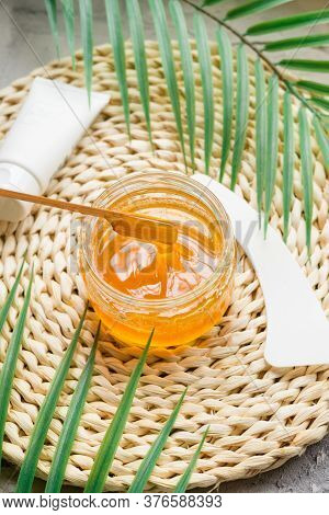 Sugar Paste To Remove Hair On A Wooden Stick. Stirring The Sugaring Paste In A Glass Jar On Wicker B