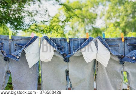 The Washed Jeans Hang On A Clothesline. Pockets Turned Inside Out. Drying Clothes On The Street. Lif