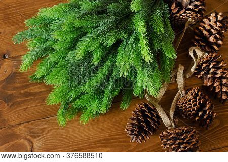 Fir Branches And Pine Cones On The Wooden Floor. Preparing Christmas Decorations.