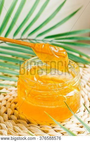 Sugar Paste For Hair Removal. Sugaring Pasta In A Glass Jar With A Wooden Stick For Mixing. Close-up