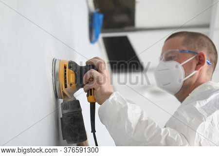 Close-up Of Professional Worker Wearing White Protective Face Mask And Working With Yellow Sander Ma