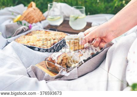 Woman Takes Homemade Cinnabon By Hand On White Blanket Outdoors. Picnic Composition With Two Glasses
