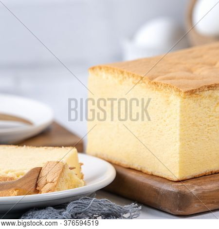 Plain Classic Taiwanese Traditional Sponge Cake (taiwanese Castella Kasutera) On A Wooden Tray Backg